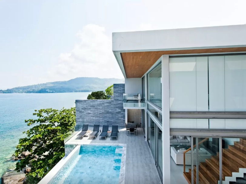 Airbnb mansion with infinity pool four sun bathing chair facing towards a clear blue sea