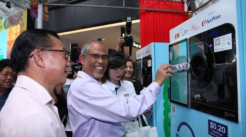 Minister with a huge grin recycling can in the smart vending machines photographed by the media